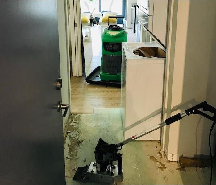 Kitchen and laundry area of an apartment with SERVPRO equipment shown removing humidity and flooring