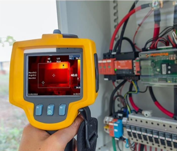 Hand-held infrared camera checking moisture in a server