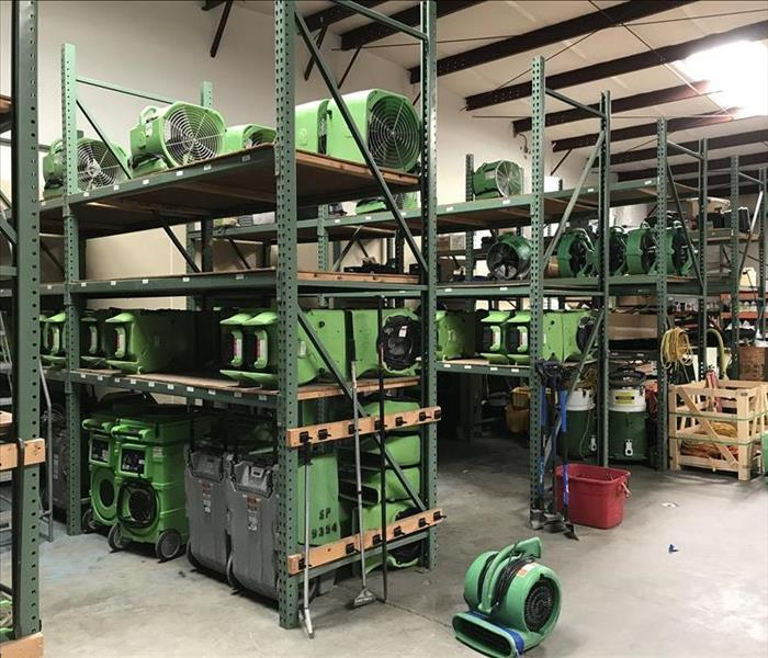 Shelves of flood damage equipment being stored in a warehouse