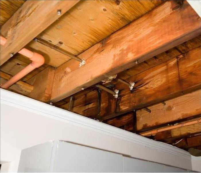 Ceiling with drywall removed, exposing the wood framing, copper pipes and PVC pipes