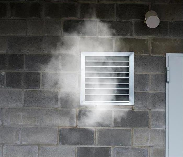 Concrete wall with a vent that has smoke coming out of it