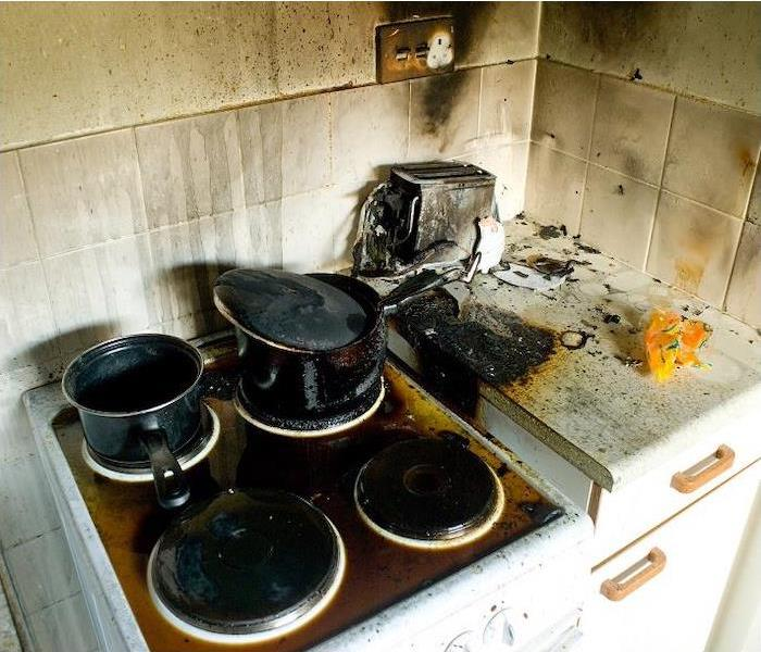 Burned pans on stove. Smoke and soot on wall.