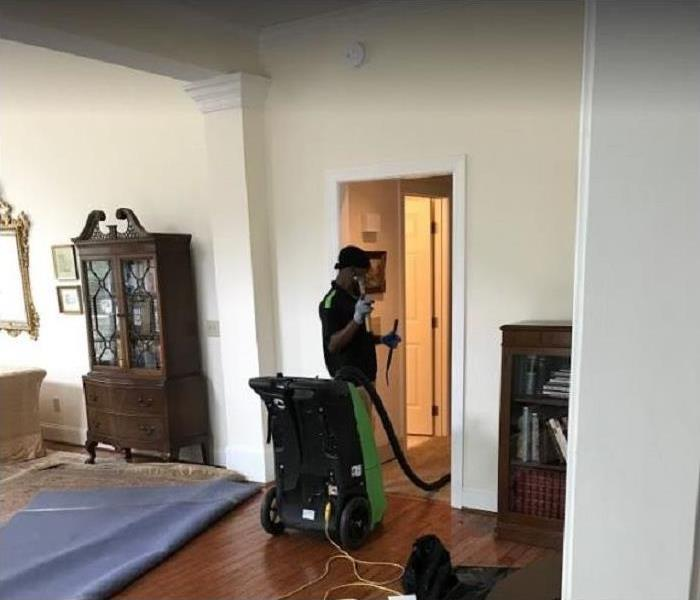 SERVPRO tech using water removal equipment in flooded home