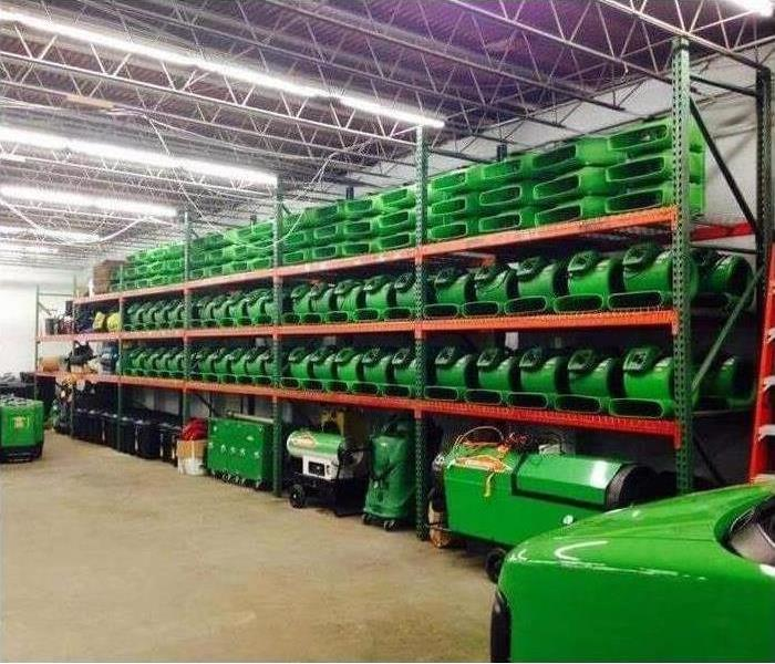 Green equipment stored on shelves in warehouse